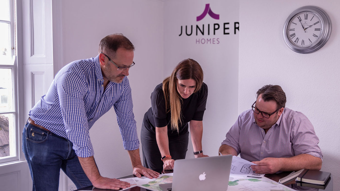 Shot of the Juniper team around a table looking at plans